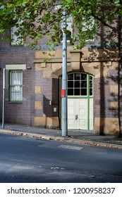 A white door into a brick and sandstone building on a sloping street. In front is a lamp post and a tree which are casting shadows in the brick wall.