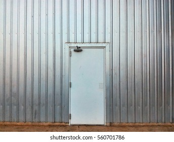 white door in old and dirty metal wall  on dirty concrete for background