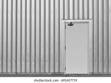 white door in old and dirty metal wall  on dirty concrete for background in black and white photography