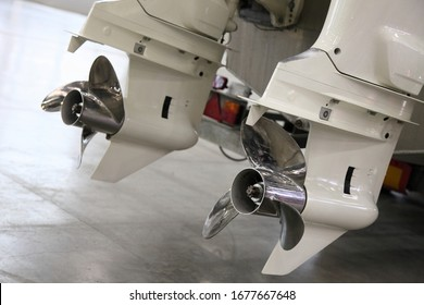 White double 200 hp outboard motor boat installation, underwater gears with stainless steel boat propellers close up