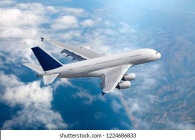 White double decker passenger plane in flight. Aircraft fly high above the sea coast. Aerial view.