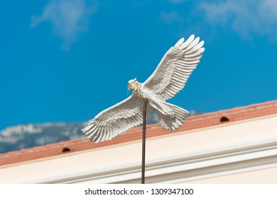 white dove sculpture on a pole in front of the princes' palace in Monaco