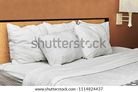 White down pillows leaning against a headboard on a made bed