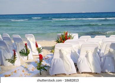 white draped chairs awaiting a Mexican beach wedding