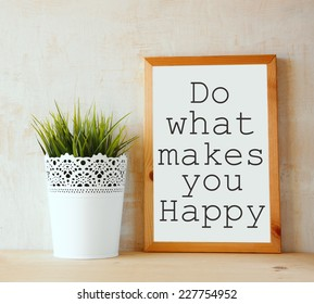 """white drawing board with the phrase """" do whats makes you happy """" written on it against textured wall"""