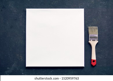 White drawing canvas with painting brush on dark background. Flat lay, top view, copy space.