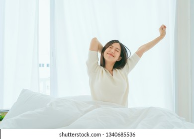 white dress asian beautiful woman stretching morning wake up bedroom with white curtain background lifestyle home concept
