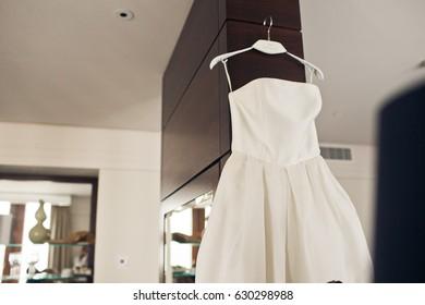 White dress hangs before bright window in blue hotel room