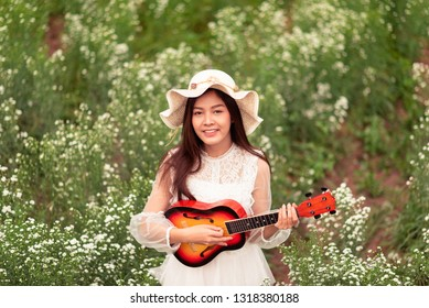 93c963d50f White dress pretty Asian girl wearing a hat and playing ukulele at the  white flowers field