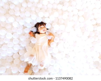 white dressed a girl plays in a pool which filled balls.