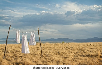White dresses hanging on a line in a rural mountain landscape