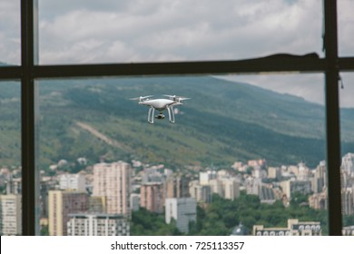 White drone with camera flying near house, shot throw glass window of skyscraper, cityscape sky and mountains on background
