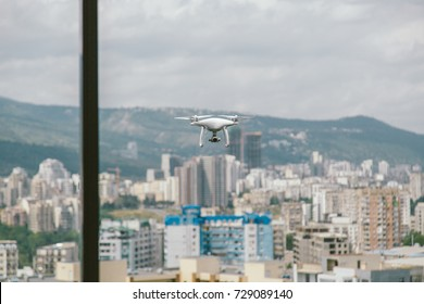 White drone with camera flying near house with glass windows