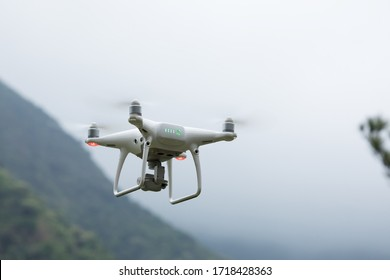 White drone with camera flying in spring mountains