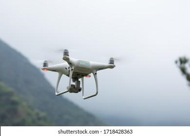 Weiße Drohne mit Kamera, die in den Frühlingsbergen fliegt