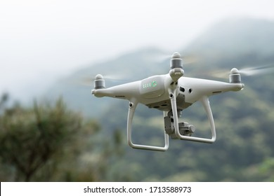 White drone with camera flying in tropical forest