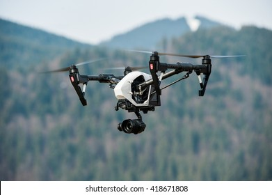 White drone with digital camera flying in sky over mountain/Drone with high resolution digital camera