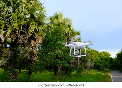 white drone fly above green ground trees road at background.