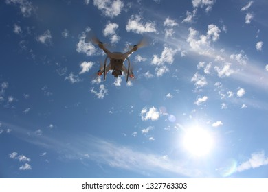 White drone fly in the blue sky and had beautiful white clouds. It was a very sunny daylight daytime.