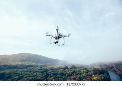 white drone flying above autumn forest