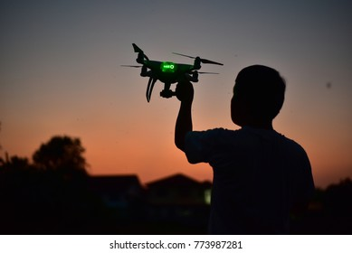 White drone in hand for take aerial photo. at dark night sihuoette control by remote.
