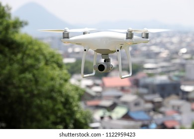 White drone with high resolution digital camera flying hovering over the city, cityscape of Kagawa, Japan
