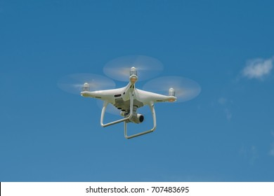 white drone hovering in a bright blue sky, Radio control helicopter