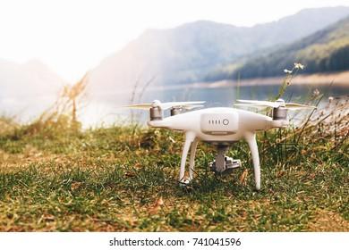 White drone on the meadow near Lake Vidraru at Fagaras Mountains. Romania