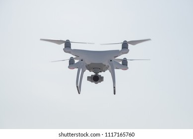 White Drone with propellers flies in the sky and photographs landscapes