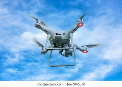White drone quadcopter taking off from the ground on background of blue sky.