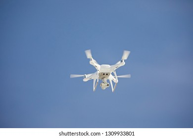 White drone quadrocopter flying against a blue sky