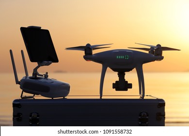white drone and remote controller, tool for aerial photo and video against sunset seascape background