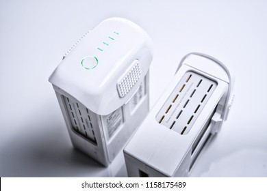 A white drone smart Battery pack with LED indicator lights ON, on white isolated background