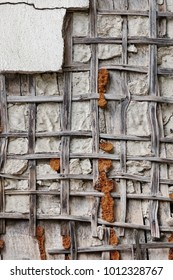 White Dry Plastered Wall With Wooden Mesh Texture. Old Wall With Damaged Broken Vertical Background.