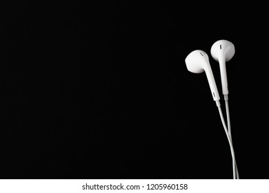 White Earbuds or Earphones on black background. Copy paste space