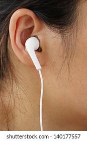 White Earphones in a Girl's Ear