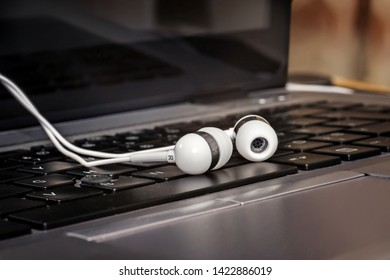White earphones on a laptop keyboard. Close up.