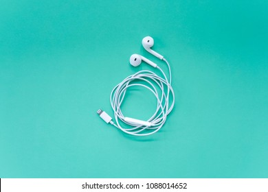 White Earphones on Turquoise Background Top View