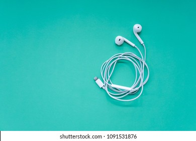 White Earphones on Turquoise Background Top View with Copy Space