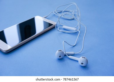 White Earphones with Tangle Cable Plugs into Smartphone on Blue Background