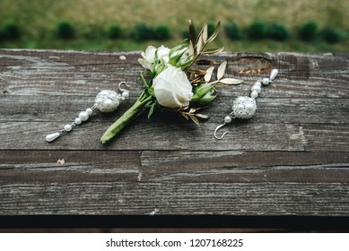 White earrings of the bride lie with flowers on a wooden background
