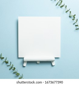 White easel blank canvas with eucalyptus leaves isolated on blue background. top view, copy space