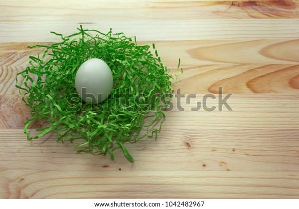 white easter  egg in green nest on wooden background