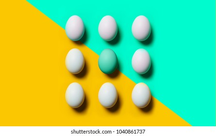 White Easter eggs on pastel peach and green background with one egg in pastel green color. Easter elements. Easter background. Easter pattern. Top view. Flat lay. Minimal concept.