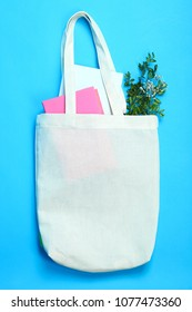 White eco bag with book and plant on a blue background.