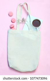 White eco bag, French macarons and a cup of tea on a pink background.