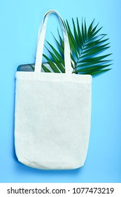 White eco bag with a tablet and a tropical leaf on a blue background.