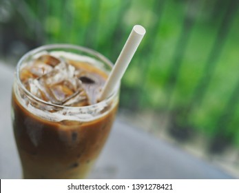 White eco friendly biodegradable paper drinking straw in a glass of iced caramel latte on blurred dark grey table with green nature background. Environmental awareness, Refreshing summer drink theme.