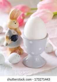 White egg in egg cup with bunny for Easter, selective focus