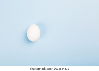 White egg on blue background. Top view, copy space